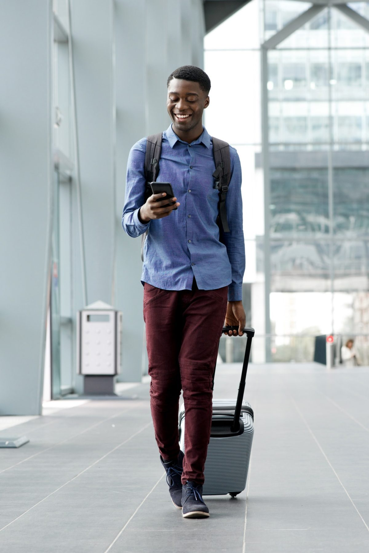 Full body young man traveling with bag and mobile phone at station