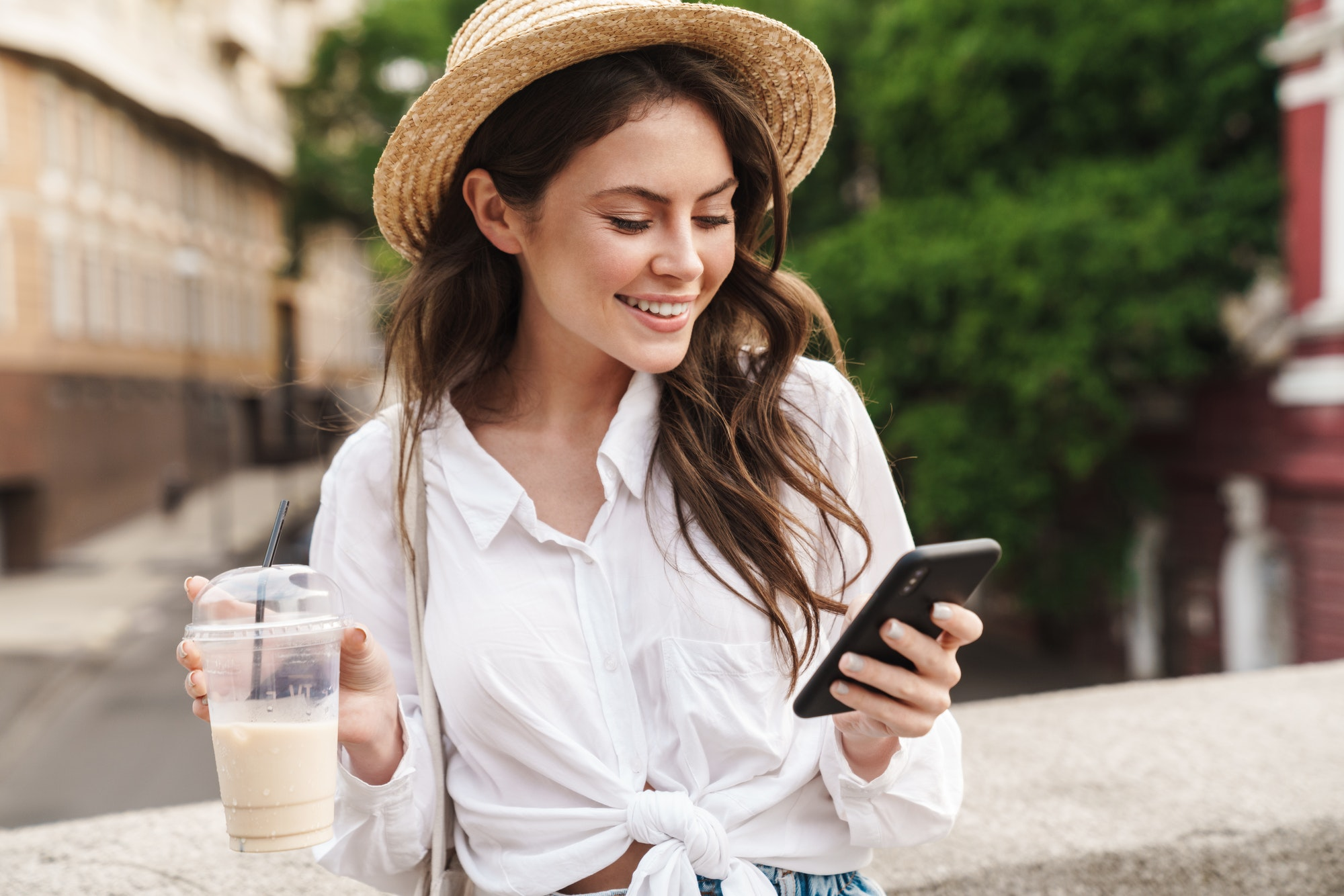Portrait of young joyful woman using cellphone and drinking milkshake