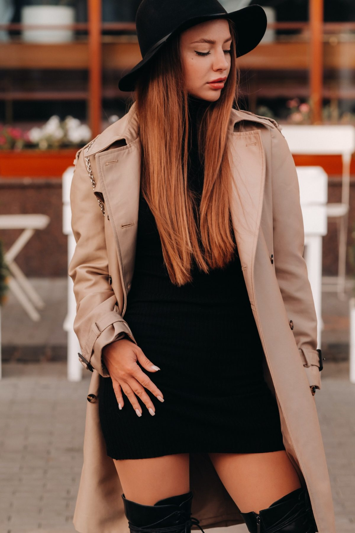 Stylish young woman in a beige coat in a black hat on a city street. Women's street fashion